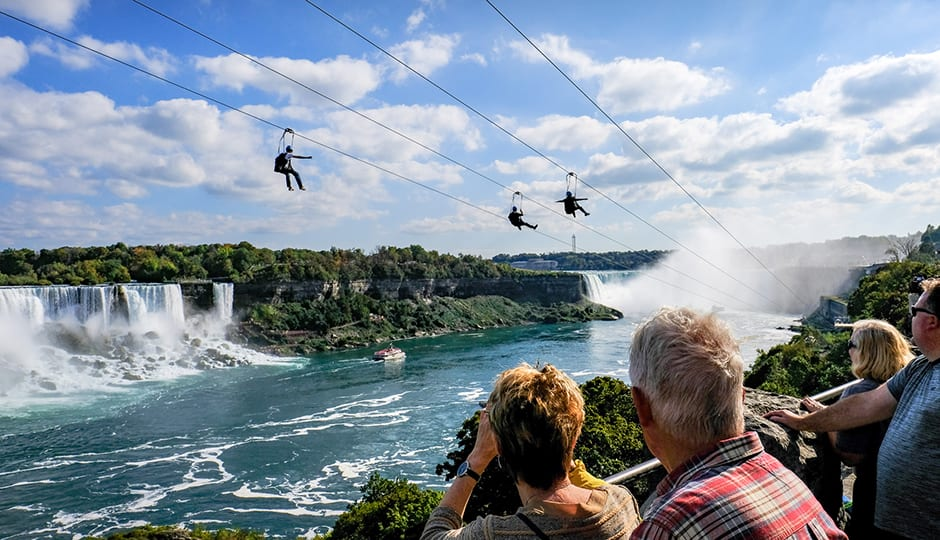 Niagara, Ontario, Canada, October 5 2016: Abstract view showing a zip wire attraction near the tourist destination of Niagara Falls, Canada. The image shows three people sliding down the zip wire with members of the public watching in the foreground. The background shows the famous landmark of Niagara falls and the white water river. Also seen near the middle is a sightseeing vessel seen near the base of there falls.