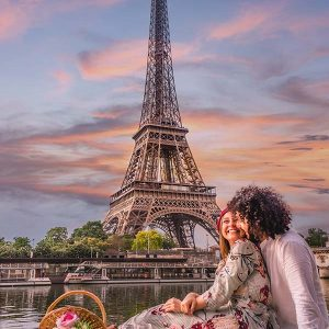 PARIS, FRANCE - Jun 07, 2019: A happy couple is celebrating love with a picnic, wine and flowers with the view of the Eiffel Tower and the Seine river at sunset.